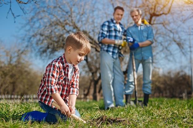 그의 아버지와 할아버지가 그를보고 뒤에 스테인리스 국자로 토양을 파고있는 동안 무릎에 서있는 어린 소년에 중점을 둡니다.