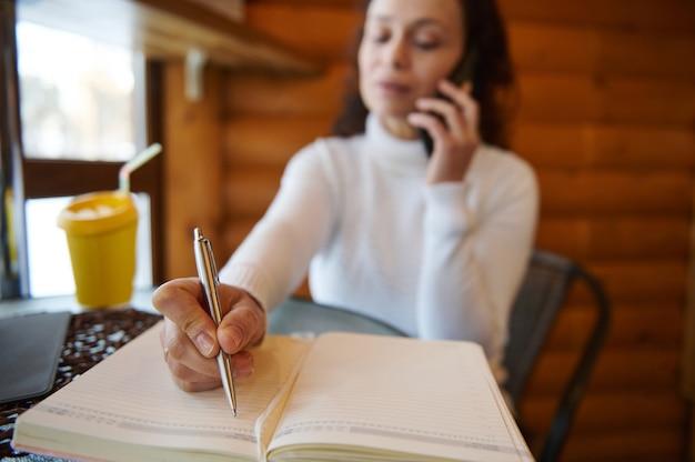 Сосредоточьтесь на ручке в руке женщины, пишущей в дневнике во время переговоров, сидя у окна в деревянном кафе