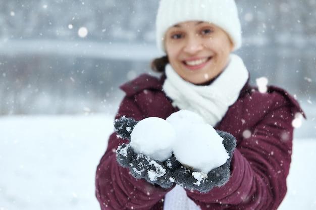 Сосредоточьтесь на руках улыбающейся женщины в серых шерстяных перчатках, держащей три снежка