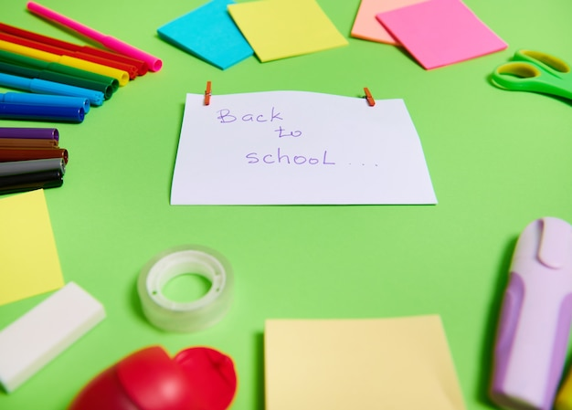 Сосредоточьтесь на белой бумаге с надписью back to school в центре разноцветного ассортимента канцелярских принадлежностей и школьных принадлежностей, расположенных по кругу. зеленый фон, копией пространства