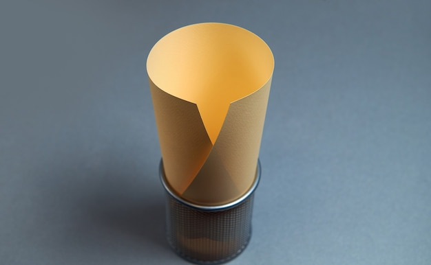 Сделайте акцент на желтой акварельной или дизайнерской бумаге в держателе для карандашей. офисные инструменты на серой поверхности