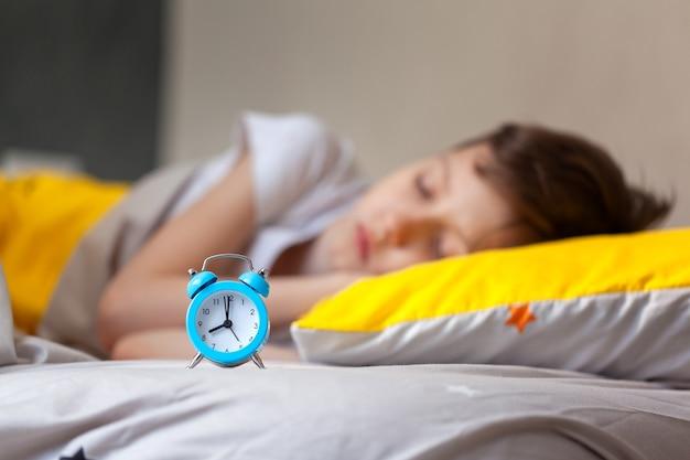 目覚まし時計に焦点を当てます。朝、目覚まし時計付きの枕の上でベッドで寝ている子供。