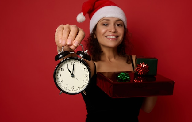 산타 모자를 쓴 흐릿한 쾌활한 여성의 손에 있는 알람 시계에 집중하고, 아름다운 이빨 미소로 웃고, 반짝이는 빨간색 녹색 선물 종이로 싸인 크리스마스 선물 상자를 들고 있습니다. 광고 공간 복사