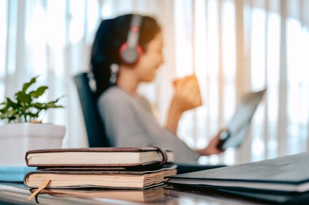 オレンジ色のカップからお茶を飲みながら家でシェアに座っている本に焦点を当てるビジネスウーマン