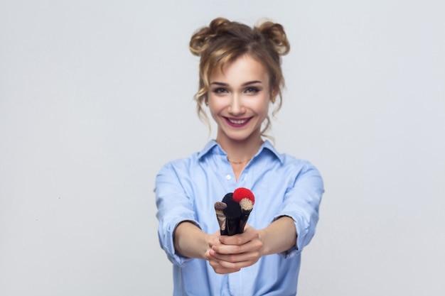 ブラシに焦点を当てます。カメラでブラシを見せて笑っている幸せの若い大人の女の子。スタジオショット