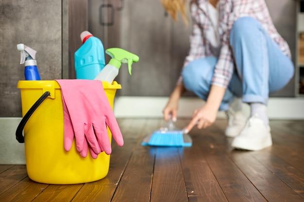 ゴム手袋と洗剤が入ったバケツに焦点を当て、女性主婦がブラシとちりとりを使って床からほこりや汚れを取り除き、家を掃除します。