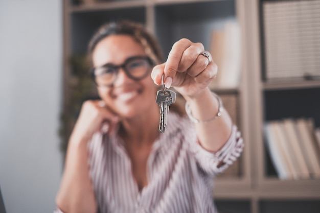 笑顔の女性の手で家の平らなアパートからの鍵の束に焦点を当てます。潜在的な買い手に新しい住居用不動産ユニットを提供する自信のある女性のプロの不動産業者のぼやけた肖像画。閉じる