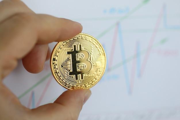 文字と金色のコインを持っているビジネスマンの手に焦点を当てる