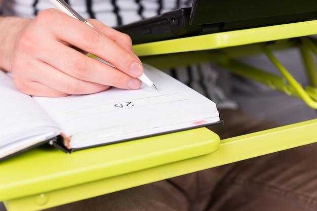 집에서 펜을 들고 소파에 앉아 사업을 하는 노트북 테이블에 누워 있는 사업가의 손 약속에 집중하세요