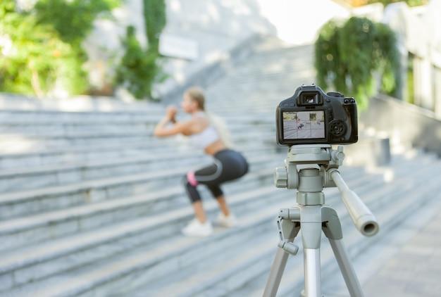 카메라에 초점을 맞춘 젊은 금발 여성은 야외에서 피트니스 고무 밴드와 함께 계단에서 점프를 연습하고 카메라에 블로그를 위한 비디오를 녹화합니다. 카메라에 초점