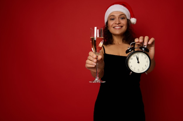 샴페인 플루트에 스파클링 와인과 알람 시계가 있는 산타 모자를 쓴 흐릿한 예쁜 여성의 손에 있는 아름다운 이빨 미소로 웃고 있습니다. 빨간색 배경에 크리스마스 개념, 복사 공간