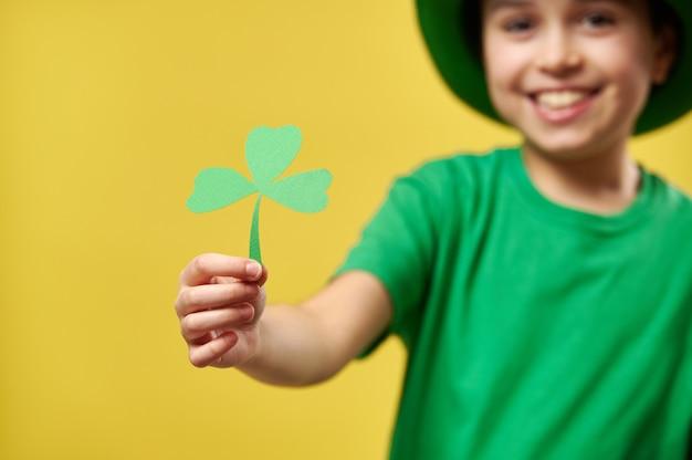 노란색 표면에 고립 된 클로버 잎을 들고 아이의 손에 초점