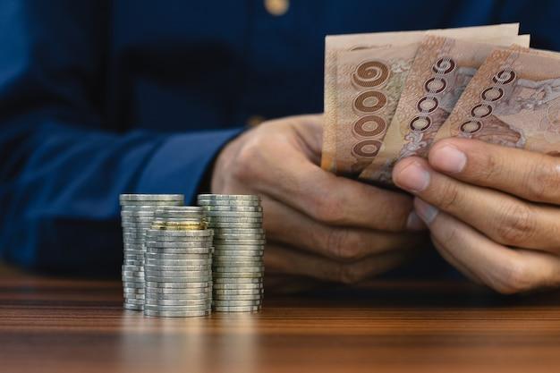 コインスタック手持ち紙幣タイバーツの背景に焦点を当て、退職のためにお金を節約する男