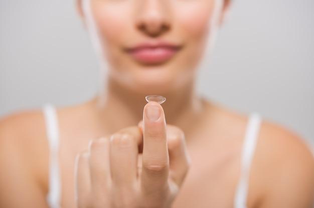 若い女性の指のコンタクトレンズに焦点を当てる