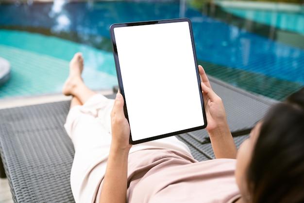 デジタルタブレットの白い画面デバイスを持っている女性の手に焦点を当てる