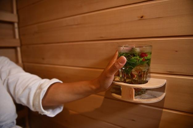 나무로 된 아늑한 사우나에서 휴식을 취하면서 비타민 음료가 든 잔을 들고 여성의 손에 집중하세요. 사우나에서 휴식을 취하는 여성의 손에 민트와 딸기가 든 물