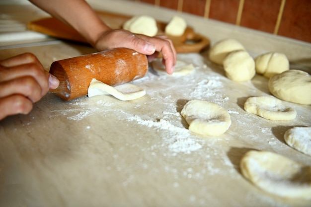 キッチンカウンターの麺棒で生地を転がす女性の手に焦点を当てて、丸い餃子の型を作ります。クローズアップ、食品の背景。餃子を段階的に調理するプロセス