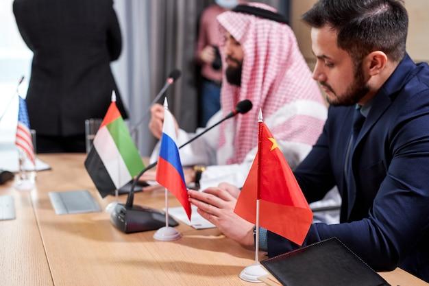 비즈니스 또는 정치 회의 중에 다른 국가의 국기에 초점을 맞추고 다양한 파트너가 의제에 대한 전략 및 아이디어를 논의하고 대화를 나눕니다.