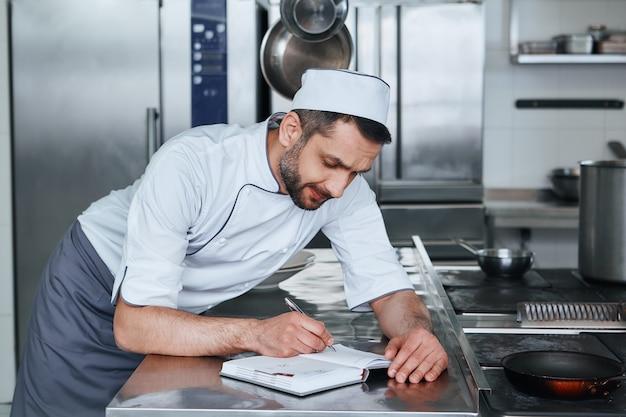 業務用厨房に立つ幸せなシェフ料理人の食品安全に焦点を当てる