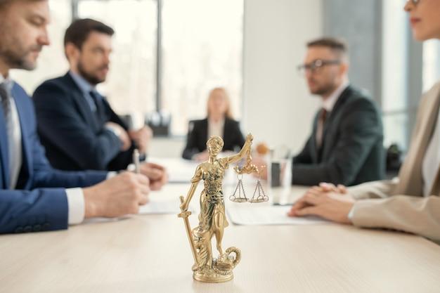 변호사 테이블에 정의의 저울과 칼날이 있는 황금 테미스에 초점을 맞추고, 동료들은 배경에서 서로 맞은편에 앉아 있습니다.