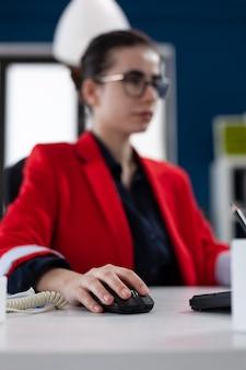 Сосредоточиться на руке бизнесвумен, держащей компьютерную мышь, работающую в корпоративном офисе предпринимателя