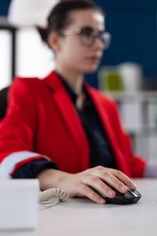 コンピューターのマウスを保持している実業家の手に焦点を当てる