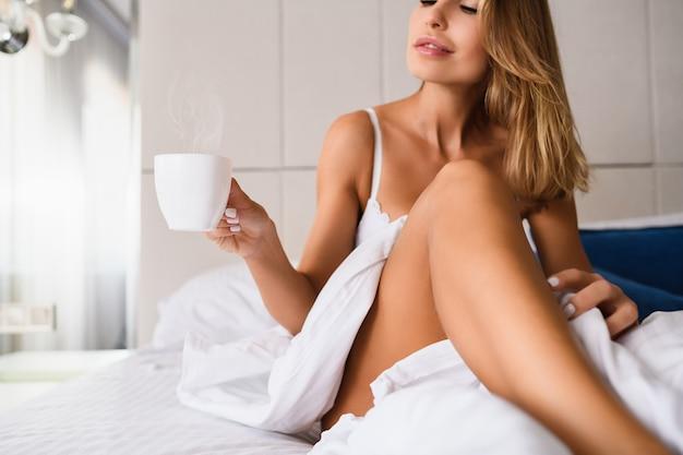흰색 커피 한잔, 실내 흰색 담요 아래 침실에 있는 섹시한 여성의 손에 든 차, 고급 주택 침대에서 아름다운 아침 식사, 호텔
