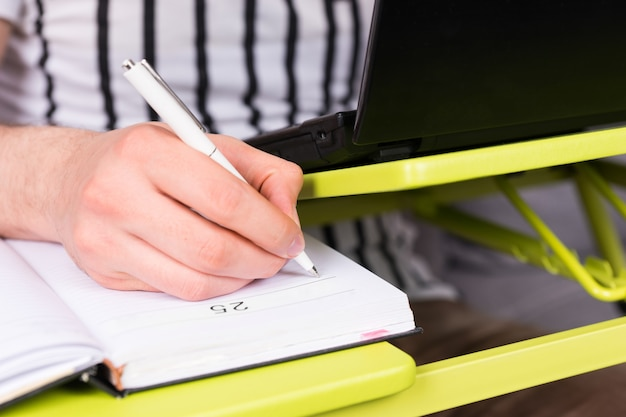 펜을 들고 소파에 앉아 집에서 그의 사업을 하는 노트북 테이블에 누워 일기를 쓰는 남자의 손에 집중하세요