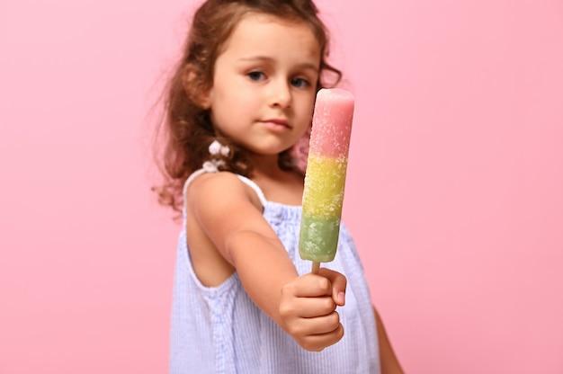 マルチカラーのカラフルなアイスキャンディー冷凍ジュース、愛らしい女の子の手のスティックにアイスクリーム、焦点が合っていない、コピースペースでピンクの背景に分離されていることに焦点を当てる