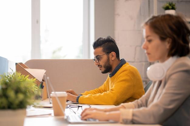 メガネをかけて机に座って広告プロジェクトに取り組んでいる深刻な忙しい若いアラビアの男性従業員に焦点を当てる