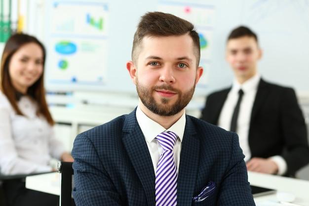 Сосредоточьтесь на умном мужчине, работающем в большом современном здании и обсуждающем важную бизнес-стратегию с младшими коллегами и сотрудниками