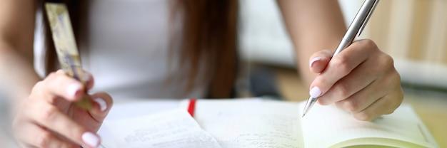 Сосредоточьтесь на нежных руках деловой женщины, которые держат металлическую ручку для письма и подсчитывают важные числа на диаграммах и графиках. концепция офиса. размытый фон