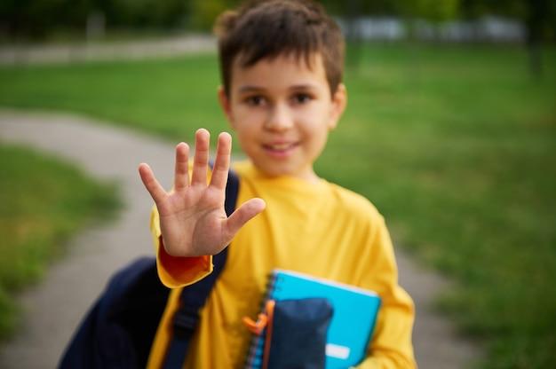 男子生徒の手のジェスチャーの停止に焦点を当てます。焦点が合っていない愛らしい男子生徒が彼の手で停止し、都市公園でバックパックと学用品を持って立っています