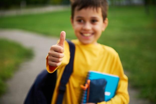親指を上にして男子生徒の手に焦点を合わせます。親指を立てて、笑顔で、バックパックと学用品を持って都市公園に立っている、焦点が合っていない愛らしい男子生徒