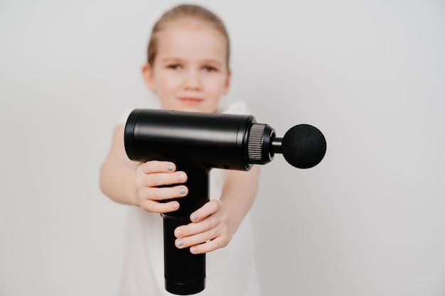主題に焦点を合わせます。子供の女の子はマッサージ銃を持っています。