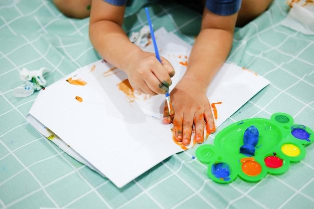 紙の上で彼らの手に焦点を合わせなさい。子供たちはブラシを使って紙に手を描き、想像力を高め、認知能力を高めます。