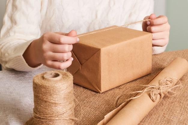 흰색 니트 스웨터 포장 상자에 여자의 손에 중점을 둡니다. 공예 포장지와 자연적인 꼬기. 행복한 휴일 선물, 놀람. 박싱 데이 선물