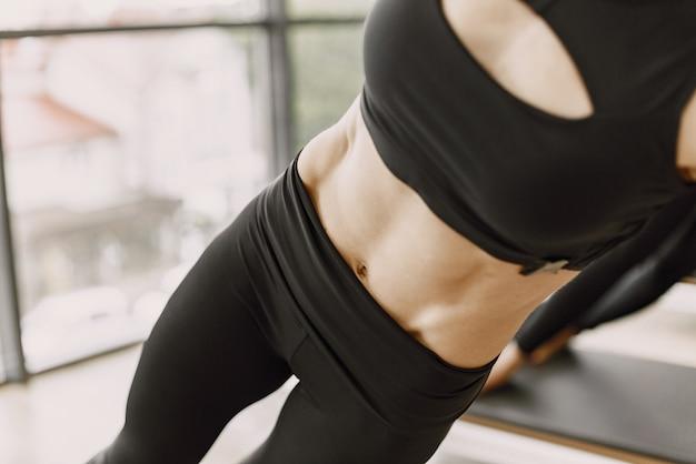 女性の胴体に焦点を当てます。ジムでトレーニングしている3人の若いフィット女性。黒のスポーツウェアを着ている女性。