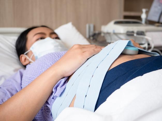 赤ちゃんをチェックするために医者を待っている医療機器を育てるベッドに横たわっている妊婦に焦点を当てる