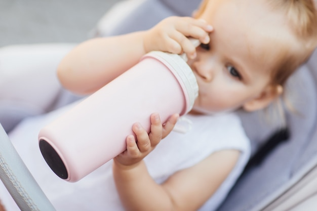 Focus at pretty girl sitting in a stroller and drinking water or milk from her thermos