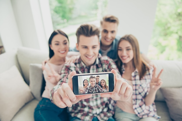 Focus on screen of modern phone with a blurry young people take selfie sit sofa