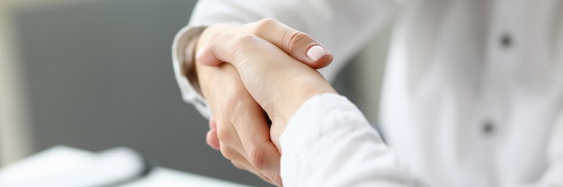 Focus on smart businesswoman arm. hand of female worker performing friendly gesture to show mutual professional affection. accounting office concept. blurred background