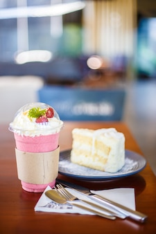 Focus strawberry smoothie water with coconut cake in a blue plate on the wooden table - de
