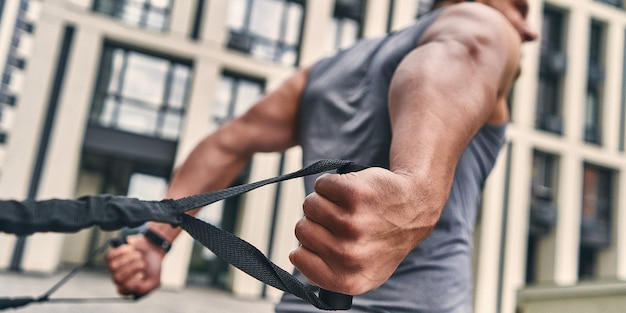 Focus on the strong muscular back of a man exercising outdoors with loops