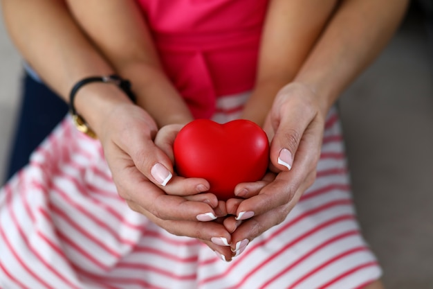 Focus on tender female hands holding baby palms and toy red heart. mother enjoying spending happy time with little daughter. family and motherhood concept
