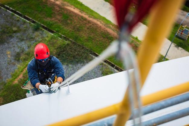탑 뷰 남성 작업자는 카라비너 로프 높이 탱크 지붕 매듭 난간 로프 접근 안전 검사를 통해 두께 저장 탱크 지붕에 초점을 맞춥니다.