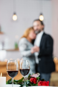 Focus on two glasses of red wine on a blurred background middle-aged couple in love