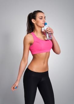 Фокус женщина пьет воду после тренировки