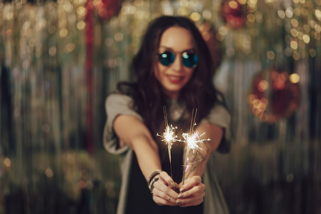 Focus on woman hands holding sparklers