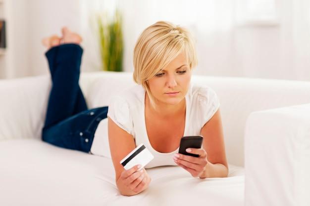 Metta a fuoco la donna che tiene il telefono cellulare e la carta di credito
